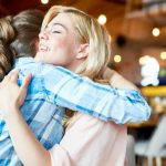 friends hugging support during infertility